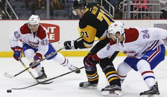 Montreal Canadiens' Phillip Danault (24) pokes the puck away from Pittsburgh Penguins' Evgeni Malkin (71) with Daniel Carr (43) helping out on defense during the second period of an NHL hockey game in Pittsburgh, Saturday, Dec. 31, 2016. (AP Photo/Gene J. Puskar)