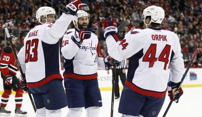 Washington Capitals center Jay Beagle (83), left wing Daniel Winnik (26) and defenseman Brooks Orpik (44) celebrate Beagle's goal against the New Jersey Devils during the first period of an NHL hockey game, Saturday, Dec. 31, 2016, in Newark, N.J. (AP Photo/Julio Cortez)