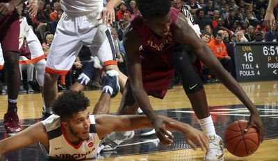 Virginia forward Isaiah Wilkins (21) reaches for the loose ball with Florida State forward Jonathan Isaac (1) during the first half of an NCAA college basketball game Saturday, Dec. 31, 2016, in Charlottesville, Va. (AP Photo/Andrew Shurtleff)