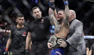 Cody Garbrandt, right, celebrates as he receives his belt after defeating Dominick Cruz, left, in a bantamweight championship mixed martial arts bout at UFC 207, Friday, Dec. 30, 2016, in Las Vegas. Garbrandt won by unanimous decision. (AP Photo/John Locher)