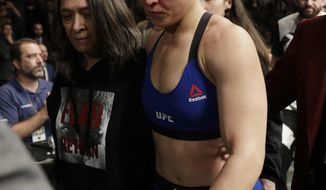 Ronda Rousey leaves the octagon after losing to Amanda Nunes in the first round of their women's bantamweight championship mixed martial arts bout at UFC 207, Friday, Dec. 30, 2016, in Las Vegas. Nunes won the fight after it was stopped in the first round. (AP Photo/John Locher)