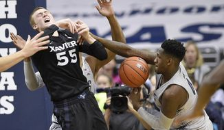 Georgetown guard L.J. Peak, right, fights for the ball against Xavier guard J.P. Macura (55) during the second half of an NCAA college basketball game, Saturday, Dec. 31, 2016, in Washington. Peak was called for a foul. Xavier won 81-76. (AP Photo/Nick Wass)