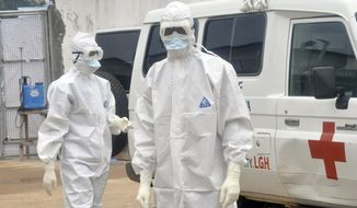 Health workers wearing protective gear wait to carry the body of a person suspected to have died from Ebola in Monrovia, Liberia, on Oct. 13, 2014. (Associated Press)