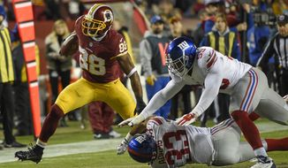 Washington Redskins wide receiver Pierre Garcon (88) breaks a tackle by New York Giants free safety Andrew Adams (33) and outside linebacker Devon Kennard (59) during the second half of an NFL football game in Landover, Md., Sunday, Jan. 1, 2017. (AP Photo/Nick Wass)