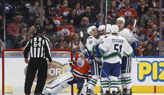 Vancouver Canucks celebrate a goal against the Edmonton Oilers during the second period of an NHL hockey game Saturday, Dec. 31, 2016, in Edmonton, Alberta. (Jason Franson/The Canadian Press via AP)