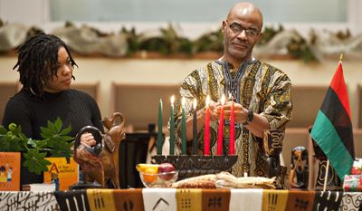 In this Tuesday, Dec. 27, 2016 photo, Jessica Stunson, left, and Clay Smalley, both of Bowling Green, light the last two candles during the 16th annual Community Kwanzaa celebration at First Christian Church, in Bowling Green, Ky. (Miranda Pederson/Daily News via AP)