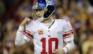 New York Giants quarterback Eli Manning celebrates running back Rashad Jennings' touchdown during the first half of an NFL football game against the Washington Redskins in Landover, Md., Sunday, Jan. 1, 2017. (AP Photo/Mark Tenally)