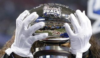 Officials place the trophy on the stage after the Peach Bowl NCAA college football playoff game between Alabama and Washington, Saturday, Dec. 31, 2016, in Atlanta. Alabama won 24-7. (AP Photo/John Bazemore)