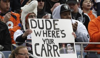"""A Denver Broncos fan holds a sign that reads """"Dude Where's Your Carr"""" in reference to the comedy movie """"Dude, Where's My Car?"""" about injured Oakland Raiders quarterback Derek Carr during in the first half of an NFL football game, Sunday, Jan. 1, 2017, in Denver. The Raiders started quarterback Matt McGloin in place of Carr in the game. (AP Photo/Joe Mahoney)"""