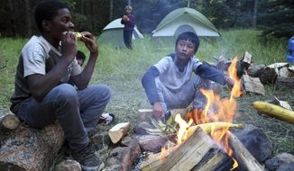 In this Sept. 10, 2016, photo, Justin Mbelechi, 13, and Bidesh Magar, 14, roast corn at their campsite in Evergreen, Colo. The two belong to a Colorado Boy Scout troop that is made up almost entirely of refugees. At campouts, traditional American food like hot dogs and trail burgers is replaced by fish head stew, fire-roasted corn and Chatpate, a popular Nepalese street snack. (AP Photo/Thomas Peipert)