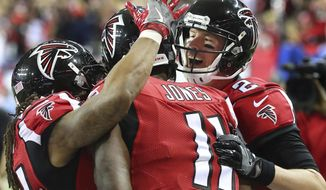 Atlanta Falcons quarterback Matt Ryan, right, and running back Devonta Freeman celebrate Ryan's touchdown pass to Julio Jones, center, against the New Orleans Saints during the second quarter of an NFL football game Sunday, Jan. 1, 2017, in Atlanta. (Curtis Compton/Atlanta Journal-Constitution via AP)