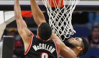 Minnesota Timberwolves forward Karl-Anthony Towns (32) attempts to block Portland Trail Blazers guard C.J. McCollum's shot during the first quarter of an NBA basketball game in Minneapolis, Sunday, Jan. 1, 2017. (AP Photo/Andy Clayton-King)