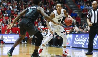 Cincinnati's Troy Caupain (10) sets up a play against Tulane's Ray Ona Embo (3) in the first half of an NCAA college basketball game, Sunday, Jan. 1, 2017, in Cincinnati. (AP Photo/John Minchillo)