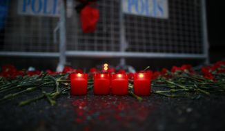Candles are lit for the victims outside a nightclub which was attacked by a gunman overnight, in Istanbul, on New Year's Day, Sunday, Jan 1, 2017. An assailant armed with a long-barrelled weapon, opened fire at a nightclub in Istanbul's Ortakoy district during New Year's celebrations, killing dozens of people and wounding dozens of others in what the province's governor described as a terror attack. (AP Photo/Emrah Gurel)