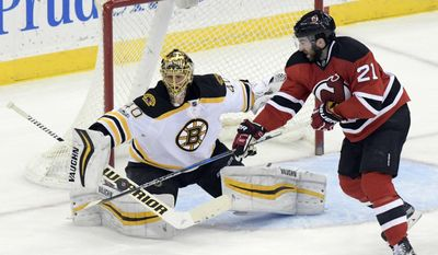 New Jersey Devils' Kyle Palmieri, right, attempts to deflect the puck as Boston Bruins goaltender Tuukka Risk makes a save during the second period of an NHL hockey game Monday, Jan. 2, 2017, in Newark, N.J. (AP Photo/Bill Kostroun)