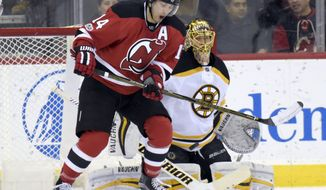 New Jersey Devils' Adam Henrique, left, deflects the puck in front of Boston Bruins goaltender Tuukka Risk during the first period of an NHL hockey game Monday, Jan. 2, 2017, in Newark, N.J. (AP Photo/Bill Kostroun)