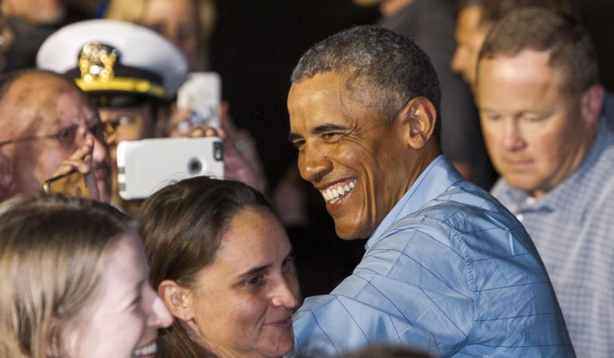 U.S. President Barack Obama greets people as he leaves Joint Base Pearl Harbor-Hickam, adjacent to Honolulu, Hawaii, en route to Washington, Sunday, Jan. 1, 2017, after his annual family vacation on the island of Oahu. (AP Photo/Marco Garcia)