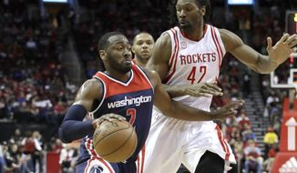 Washington Wizards' John Wall (2) drives toward the basket as Houston Rockets' Nene Hilario (42) defends during the first half of an NBA basketball game Monday, Jan. 2, 2017, in Houston. (AP Photo/David J. Phillip)
