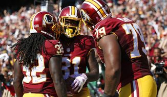 Robert Kelley, left, Matt Jones, center, and Ty Nsekhe celebrate Jones' touchdown in October. Kelley eventually replaced Jones as the Redskins' lead back and could handle the position next season, too. / AP photo