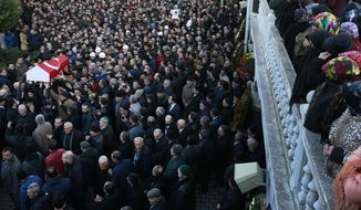 Mourners watch as others carry the Turkish flag-draped coffin of Yunus Gormek, 23, one of the victims of the attack at a nightclub on New Year's Day, during the funeral in Istanbul, Monday, Jan. 2, 2017. Turkey's state-run news agency says police have detained eight people in connection with the Istanbul nightclub attack. The gunman, who escaped after carrying out the attack, wasn't among the eight. The Islamic State group has claimed responsibility for the attack, which killed 39 people, most of them foreigners. (AP Photo/Emrah Gurel)