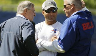 FILE - In this June 3, 2015, file photo, Buffalo Bills owner Terry Pegula, left, general manager Doug Whaley, center, and coach Rex Ryan talk on the sidelines during an NFL football practice  in Orchard Park, N.Y. The Rex Effect in Buffalo lasted less than two full seasons, and now the Bills are in the familiar spot of opening a new year by launching yet another coaching search. (AP Photo/Gary Wiepert, File)