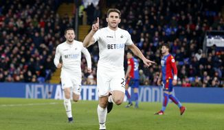 Swansea City's Angel Rangel, centre, celebrates after scoring the winning goal during the English Premier League soccer match between Crystal Palace and Swansea City at Selhurst Park stadium, in London, Tuesday, Jan. 3, 2017.  Swansea won the match 2-1. (AP Photo/Alastair Grant)