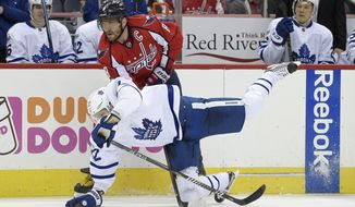 Toronto Maple Leafs defenseman Nikita Zaitsev, front, of Russia, gets tripped up by Washington Capitals left wing Alex Ovechkin (8), of Russia, during the second period of an NHL hockey game, Tuesday, Jan. 3, 2017, in Washington. (AP Photo/Nick Wass)