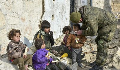 This undated handout photo released by the Russian Defense Ministry claims to show a Russian Military engineer distributing juice to local children in Aleppo, Syria.(Russian Defense Ministry Press Service photo via AP)