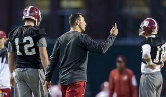 Alabama offensive coordinator Steve Sarkisian works with his players during football practice, Tuesday, Jan. 3, 2017, at the Thomas-Drew Practice Fields in Tuscaloosa, Ala. Seen in picture are Alabama quarterback David Cornwell (12) and Alabama quarterback Cooper Bateman (18). (Vasha Hunt/AL.com via AP)