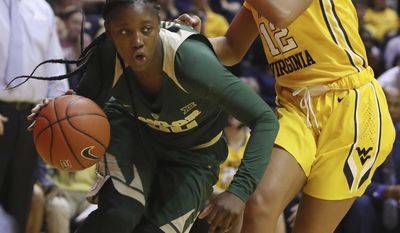 Baylor guard Alexis Jones (30) drives pass West Virginia guard Chania Ray (12) during the second quarter of an NCAA college basketball game, Wednesday, Jan. 4, 2017, in Morgantown, W.Va. (AP Photo/Raymond Thompson)