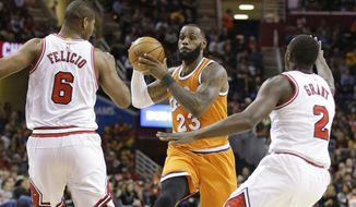 Cleveland Cavaliers' LeBron James (23) drives between Chicago Bulls' Cristiano Felicio (6), from Brazil, and Jerian Grant (2) in the first half of an NBA basketball game, Wednesday, Jan. 4, 2017, in Cleveland. (AP Photo/Tony Dejak)