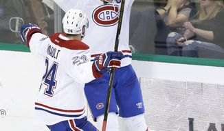 Montreal Canadiens left wing Max Pacioretty (67) celebrates scoring the game winning goal with teammates Phillip Danault (24) during overtime of NHL hockey game against the Dallas Stars in Dallas, Wednesday, Jan. 4, 2017. The Canadiens won 4-3. (AP Photo/LM Otero)