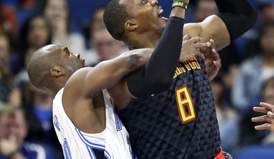 Atlanta Hawks' Dwight Howard, right, is fouled by Orlando Magic's Jodie Meeks, left, as he attempts a shot during the first half of an NBA basketball game, Wednesday, Jan. 4, 2017, in Orlando, Fla. (AP Photo/John Raoux)