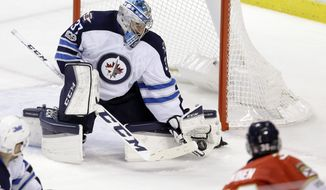Winnipeg Jets goalie Connor Hellebuyck (37) blocks a shot by Florida Panthers left wing Jussi Jokinen (36) during the second period of an NHL hockey game, Wednesday, Jan. 4, 2017, in Sunrise, Fla. (AP Photo/Alan Diaz)