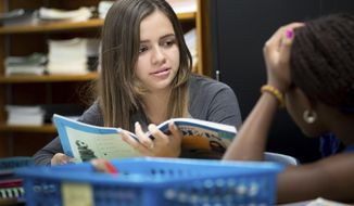 This photo taken Nov. 28, 2016, shows Arianna Sosa, a high school student from El Salvador, mentoring another student in Omaha, Neb.  Immigrant students who want to learn English have been getting help from other Ralston students who also struggled with their new language. (Matt Miller/The World-Herald via AP)