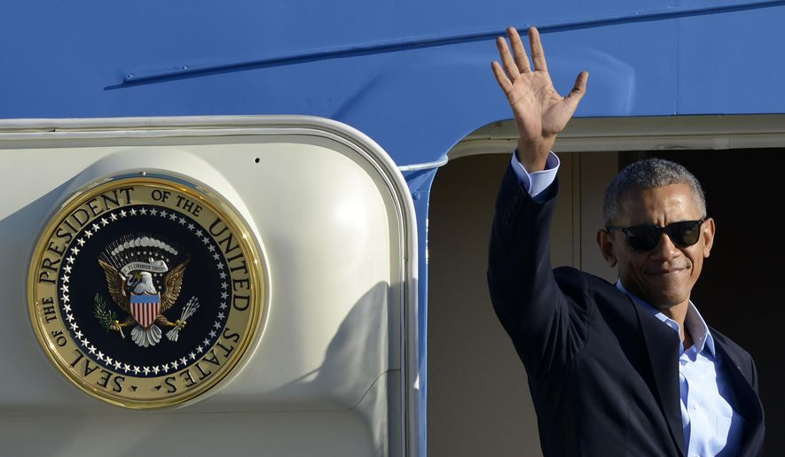In this Oct. 9, 2016, file photo, President Barack Obama, wearing sunglasses, waves while boarding Air Force One before leaving O'Hare International Airport in Chicago.  (AP Photo/Paul Beaty, File)