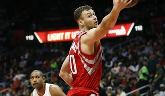 FILE - In this March 19, 2016, file photo, Houston Rockets forward Donatas Motiejunas (20) grabs a rebound in the first half of an NBA basketball game against the Atlanta Hawks in Atlanta. The 7-footer from Lithuania, who has played four previous NBA seasons with Houston, signed a free-agent contract with the Pelicans on Tuesday and practiced with the team for the first time on Wednesday, Jan. 4, 2017. He has had back problems in recent seasons but said he is healthy now and ready to contribute immediately. (AP Photo/John Bazemore, File)