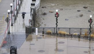 A woman walks in the rain in downtown Reno, Nevada on Wednesday, Jan. 4, 2017, across a bridge above the rising waters of the Truckee River. A flash flood was in effect in Reno 40 miles downstream from Lake Tahoe, where a winter storm warning continued and another foot of snow in the Sierra was expected. (AP Photo/Scott Sonner)