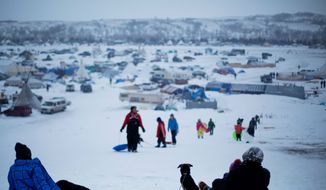 FILE - In this Thursday Dec. 1, 2016 file photo, the Oceti Sakowin camp where people have gathered to protest the Dakota Access oil pipeline stands in the background as a children sled down a hill in Cannon Ball, N.D. Some Native Americans worry the transition to a Donald Trump administration signals an end to eight years of sweeping Indian Country policy reforms. But Trump's Native American supporters said they're hopeful he will cut through some of the government red tape that they believe has stifled economic progress on reservations. (AP Photo/David Goldman, File) **FILE**