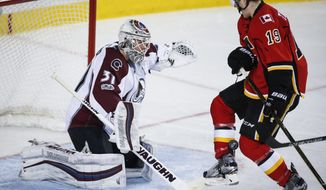 Colorado Avalanche goalie Calvin Pickard, left, looks on as the puck gets caught in the legs of Calgary Flames' Matthew Tkachuk during the third period of an NHL hockey game, Wednesday, Jan. 4, 2017, in Calgary, Alberta.  (Jeff McIntosh/The Canadian Press via AP)