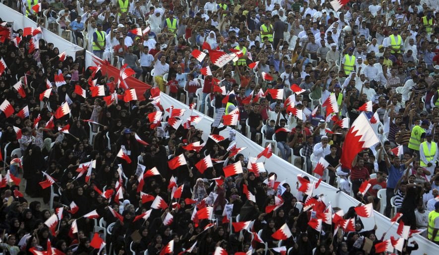 FILE- In this Friday, Sept. 30, 2011 file photo, Bahraini anti-government protesters wave flags and chant during a rally of thousands organized by Al-Wefaq, the largest Shiite opposition party, to demand greater freedoms in Quraya, Bahrain. Bahrain has again allowed agents of its domestic spy service to make arrests, reversing a key reform recommended in the wake of the crackdown that followed its 2011 Arab Spring protests. (AP Photo/Hasan Jamali, File)