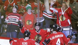 Chicago Blackhawks' Ryan Hartman, center, celebrates his goal with Tanner Kero (67) and Niklas Hjalmarsson, during the first period of an NHL hockey game against the Buffalo Sabres Thursday, Jan. 5, 2017, in Chicago. (AP Photo/Charles Rex Arbogast)