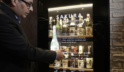 Mario Gonzalez talks about the interactive Wine and Sake Cellar at the Panasonic booth during CES International, Thursday, Jan. 5, 2017, in Las Vegas. (AP Photo/John Locher)