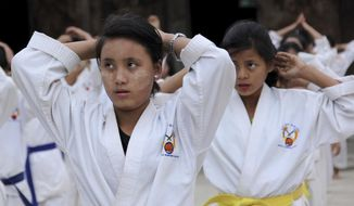 In this Nov. 29, 2016, photo, 16-year-old Hkawn Ra, joins the karate training for self-defense in Jeyang village IDP camp, near China border in Kachin State, Myanmar. Forced from their homes and in some cases torn from their families, young girls and women at a refugee camp in Myanmar's Kachin state are studying karate to help protect themselves from a known threat: the country's own military. (AP Photo/Esther Htusan)