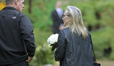 """Actress Meryl Streep arrives with flowers at a memorial service at the homes of Debbie Reynolds and her daughter Carrie Fisher in Los Angeles Thursday, Jan. 5, 2017. Reynolds died Dec. 28 at the age of 84, a day after her daughter died at the age of 60. Streep starred in the film, """"Postcards From the Edge,"""" based on Fisher's 1987 semi-autobiographical novel of the same title. (AP Photo/Reed Saxon)"""