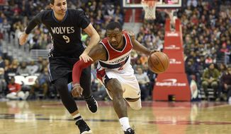 Washington Wizards guard John Wall (2) dribbles against Minnesota Timberwolves guard Ricky Rubio (9), of Spain, during the second half of an NBA basketball game, Friday, Jan. 6, 2017, in Washington. (AP Photo/Nick Wass)