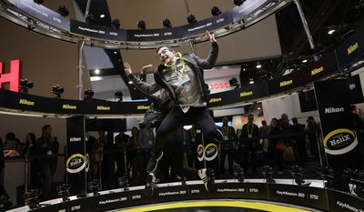 Simon Rosen jumps while having his picture taken in the Project Helix at the Nikon booth during CES International, Thursday, Jan. 5, 2017, in Las Vegas. (AP Photo/John Locher)