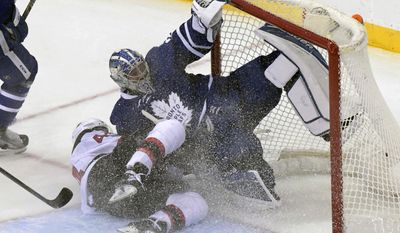 New Jersey Devils' Miles Wood, left, slides into Toronto Maple Leafs goaltender Frederik Anderson during the third period of an NHL hockey game Friday, Jan. 6, 2017, in Newark, N.J. (AP Photo/Bill Kostroun)