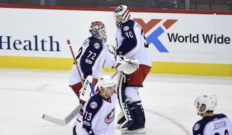 Columbus Blue Jackets goalie Sergei Bobrovsky (72), of Russia, skates toward the bench as he is replaced by goalie Curtis McElhinney (30) during the third period of an NHL hockey game against the Washington Capitals, Thursday, Jan. 5, 2017, in Washington. Blue Jackets right wing Cam Atkinson (13) and center Boone Jenner (38) look on. (AP Photo/Nick Wass)
