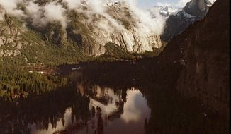 File - In this Jan. 3, 1997, file photo, the Merced River appears to form a lake in Yosemite Valley from heavy rains which melted the snow pack in Yosemite National Park, Calif. A massive storm approaching Central California could overflow rivers, trigger rockslides and send trees falling onto powerlines, putting visitors on alert in Yosemite National Park, which flooded from a 1997 storm that temporarily closed the park. (Mark Crosse/The Fresno Bee via AP, File)